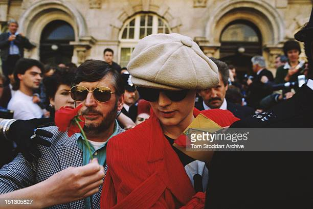 Fans hold out red roses for their idol English singersongwriter Boy George who is accompanied by a bodyguard circa 1987