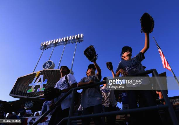 Fans hold out their gloves in centerfield for a baseball before Game Two of the National League Division Series between the Atlanta Braves and the...