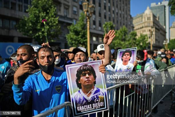 Fans hold photos of Argentinian late football legend Diego Armando Maradona outside the Casa Rosada government house as they wait to pay their...