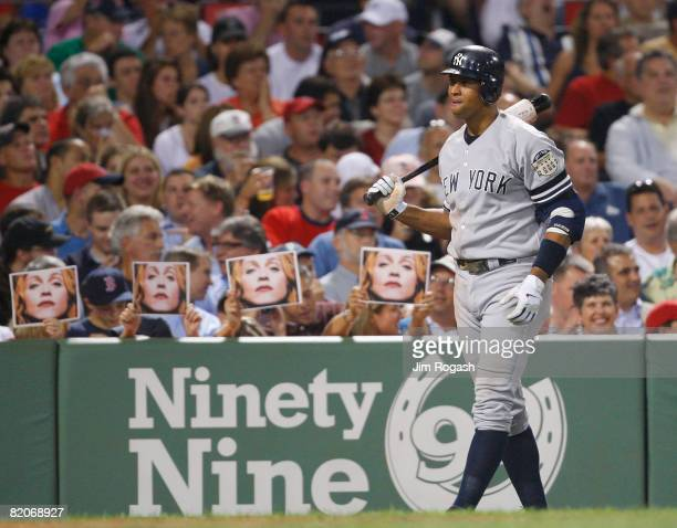 Fans hold pictures of Madonna as Alex Rodriguez of the New York Yankees prepares to bat against the Boston Red Sox at Fenway Park on July 25 2008 in...