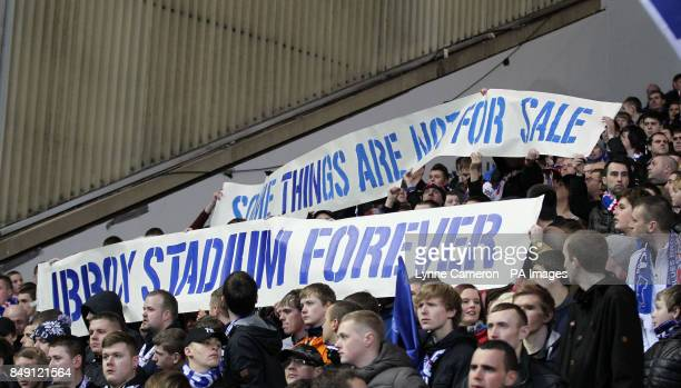 Fans hold signs against the selling of the name of Ibrox stadium Glasgow