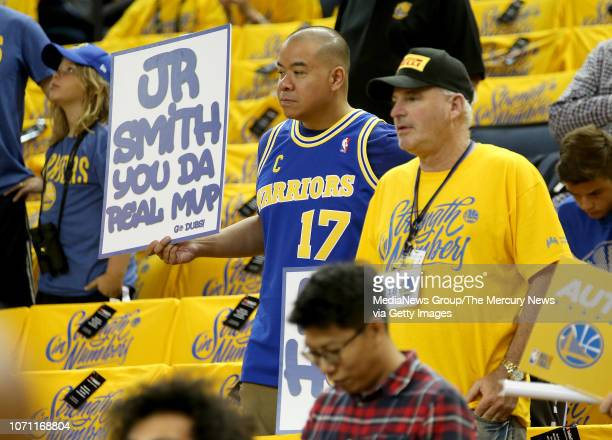 Fans hold signs as the Golden State Warriors warm up before Game 2 of the NBA Finals against the Cleveland Cavaliers at Oracle Arena in Oakland Calif...