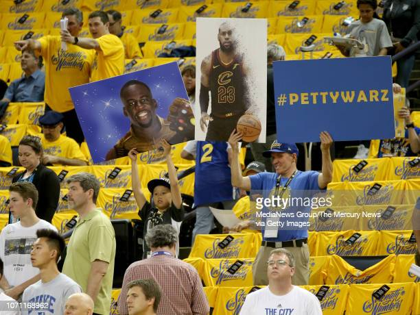 Fans hold signs during warmups before Game 2 of the NBA Finals against the Cleveland Cavaliers at Oracle Arena in Oakland Calif on Sunday June 3 2018