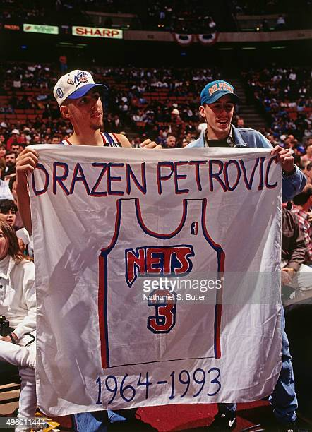 Fans hold signs in memory of Drazen Petrovic prior to a game against the Indiana Pacers on November 11 1993 at Continental Airlines Arena in East...