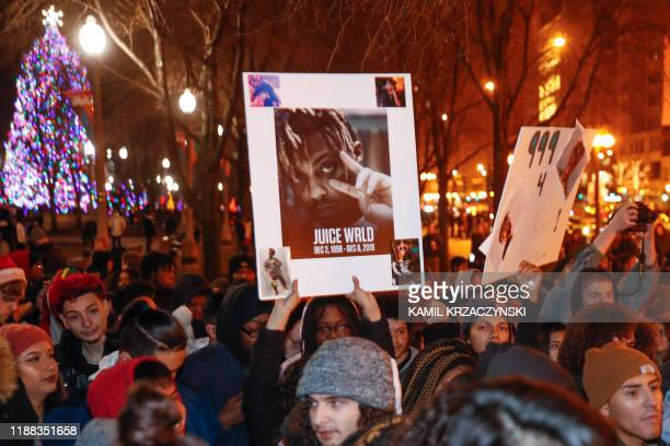 Fans hold signs in memory of rapper Juice Wrld during his Memorial at the Millennium Park on December 13 2019 in Chicago Illinois