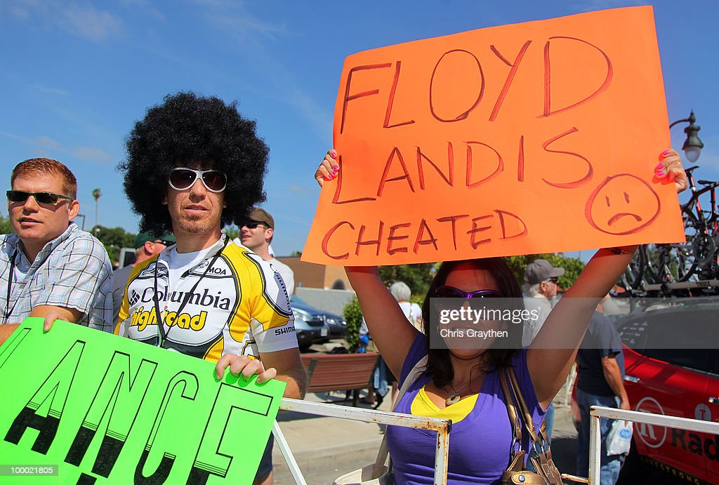 Fans hold signs in support of Armstrong and accusing Floyd Landis of cheating prior to Stage Five of the 2010 Tour of California from Visalia to Bakersfield on May 20, 2010 in Visalia, California.