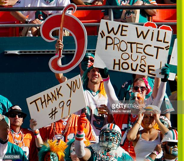 Fans hold signs in the first quarter of the Miami Dolphins game against the New York Jets at Sun Life Stadium in Miami Gardens Florida Sunday January...
