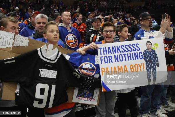 Fans hold signs regarding John Tavares of the Toronto Maple Leafs and his signing with that team this past summer at NYCB Live's Nassau Coliseum on...