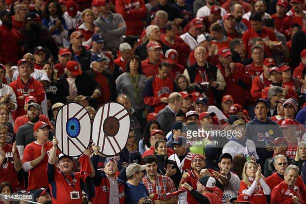 Fans hold signs showing the eyes of Max Scherzer of the Washington Nationals during game five of the National League Division Series between the Los...