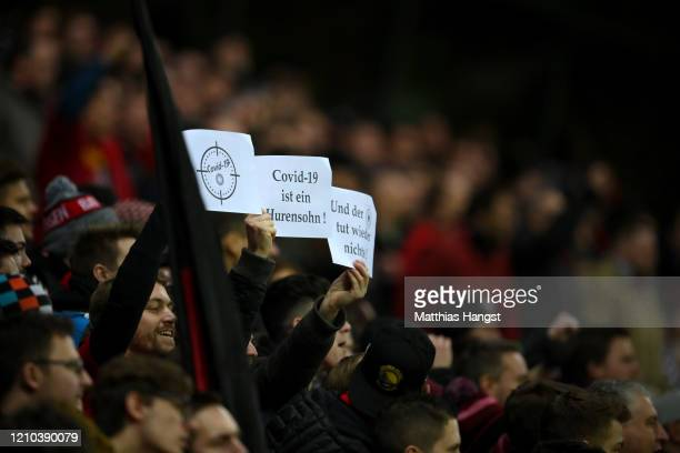 Fans hold signs with messages regarding the Covid-19 virus during the DFB Cup quarterfinal match between Bayer 04 Leverkusen and 1. FC Union Berlin...
