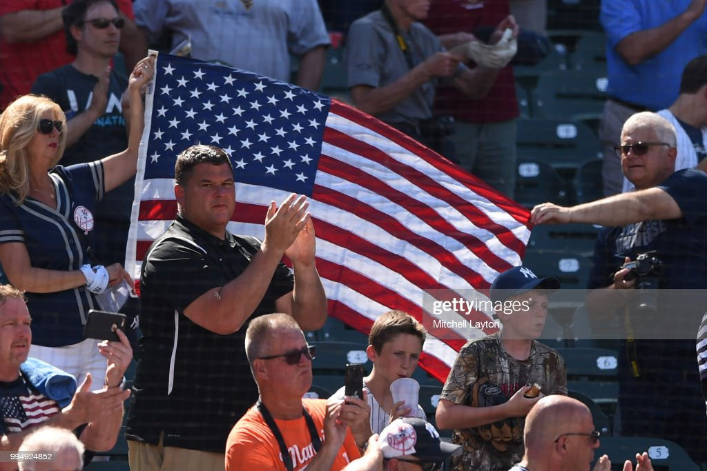 Fans hold the flag during the National Anthem during a game one of a doubleheader baseball game between the New York Yankees and the Baltimore Orioles at Oriole Park at Camden Yards on July 9, 2018 in Baltimore, Maryland.