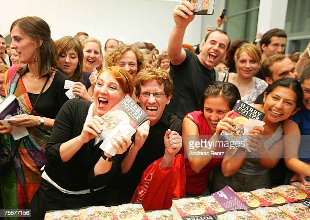 Fans hold the last book by JK Rowling Harry Potter and the Deathly Hallows in their hands at a bookstore after its release at 101am on July 21 2007...