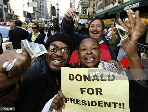 Fans hold up 100dollar bills given to the first 100 customers in line to meet real estate developer Donald Trump before Trump arrives to promote his...