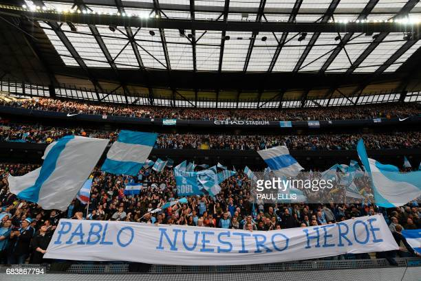 Fans hold up a banner in tribute to Manchester City's Argentinian defender Pablo Zabaleta that reads in Spanish 'Pablo Nuestro Heroe' during the...