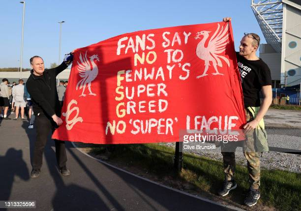 Fans hold up a protest banner against Liverpool FC and the European Super League outside the stadium prior to the Premier League match between Leeds...