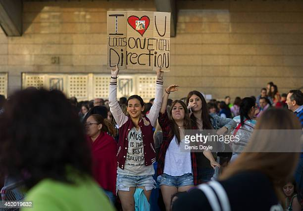 Fans hold up a sign outside the Vicente Calderon stadium while waiting for the first of two shows by the British and Irish band One Direction on July...