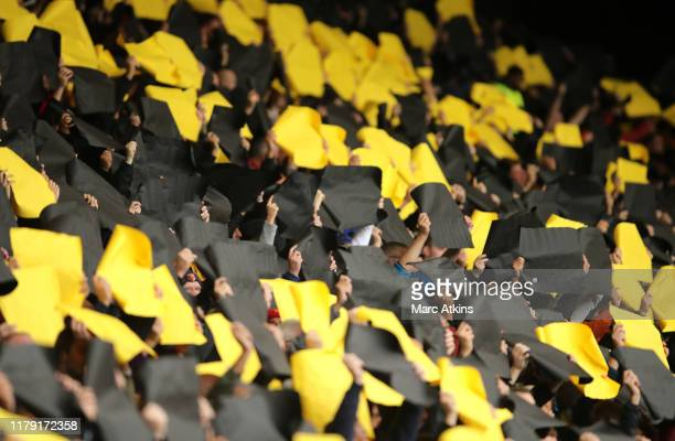Fans hold up cards to make a display photo during the Premier League match between Watford FC and Sheffield United at Vicarage Road on October 05,...