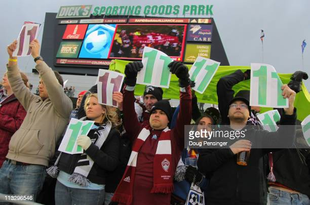 Fans hold up cards with the in burgundy and green during the 11th minute of action between the Colorado Rapids and the Chicago Fire at Dick's...