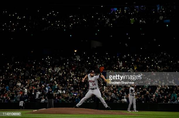 Fans hold up cellphones with lights in stands as relief pitcher Roberto Osuna of the Houston Astros warms up before the ninth inning of game against...
