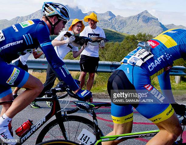 Fans hold up fish as cyclists pass by during the second stage of the Arctic Race of Norway on August 9 2013 in Svolvaer Norway AFP PHOTO / DANIEL...