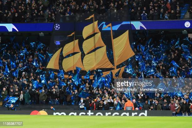 Fans hold up flags during the UEFA Champions League Round of 16 Second Leg match between Manchester City v FC Schalke 04 at Etihad Stadium on March...