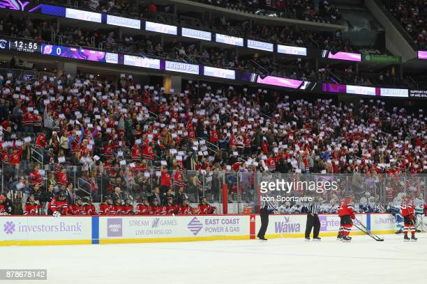 Fans hold up I Fight For Placards during the National Hockey League game between the New Jersey Devils and the Vancouver Canucks on November 24 at...