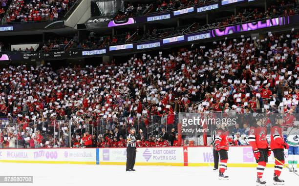 Fans hold up I fight for placards in honor of Hockey Fights Cancer night during a timeout during the game between the New Jersey Devils and the...