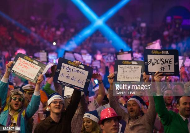 Fans hold up messages ahead of the PDC World Championship darts final between Netherlands' Michael van Gerwen and Scotland's Gary Anderson at...