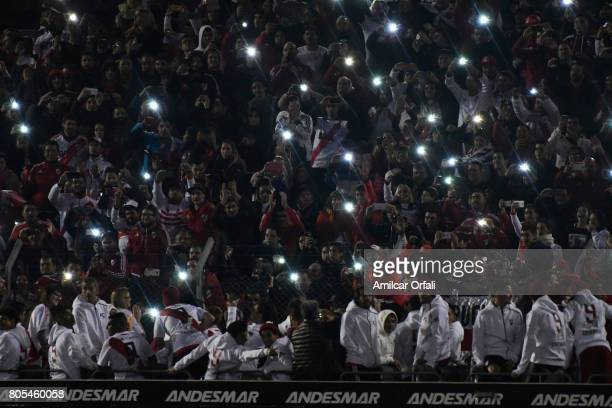 Fans hold up phones with lights during Fernando Cavenaghi's farewell match at Monumental Stadium on July 01 2017 in Buenos Aires Argentina