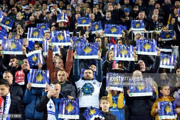 Fans hold up posters with the Kosovo flag before the UEFA Euro 2020 Group A football qualification match between Kosovo and England at the Fadil...