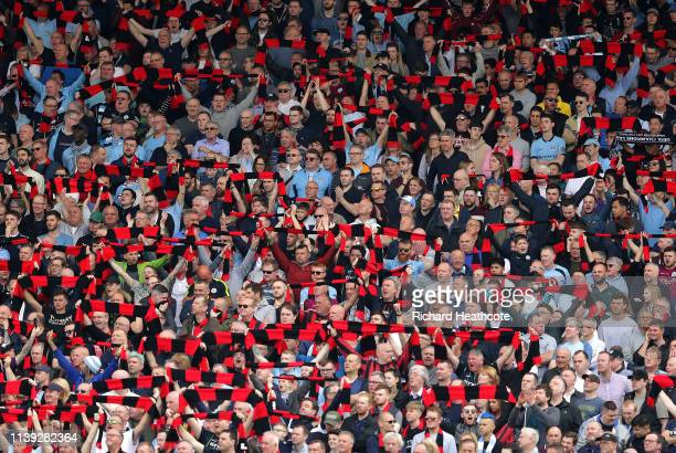 Fans hold up red and black scarves in tribute to Bernard Halford former club secretary during the Premier League match between Fulham FC and...