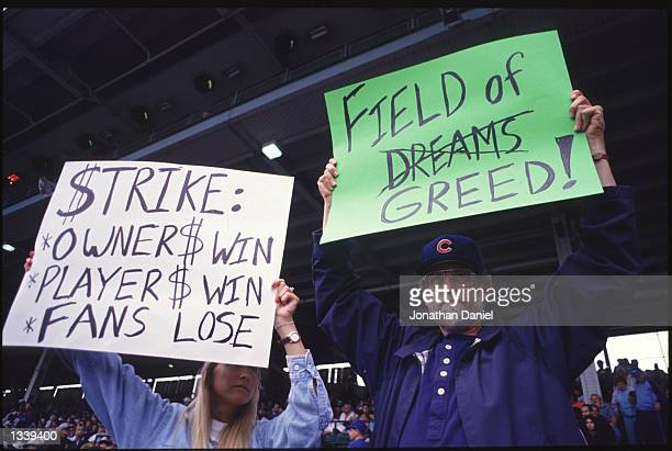 Fans hold up signs in protest of the baseball strike during a game between the San Francisco Giants and the Chicago Cubs at Wrigley Field in Chicago,...