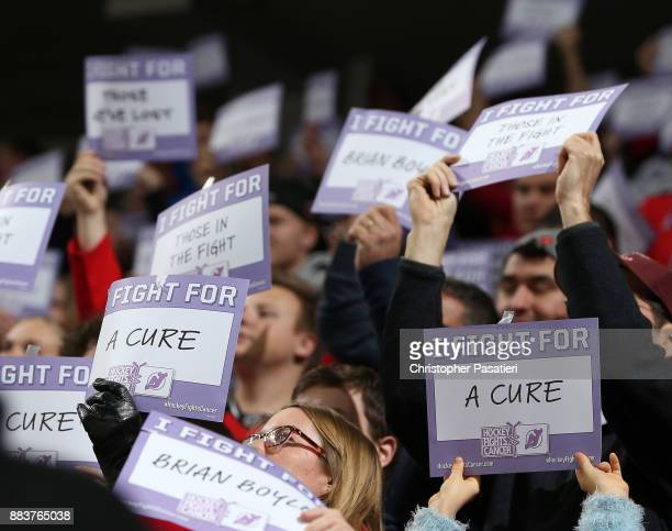 Fans hold up signs in support of Hockey Fights Cancer during the game between the Vancouver Canucks and New Jersey Devils on November 24 2017 at the...