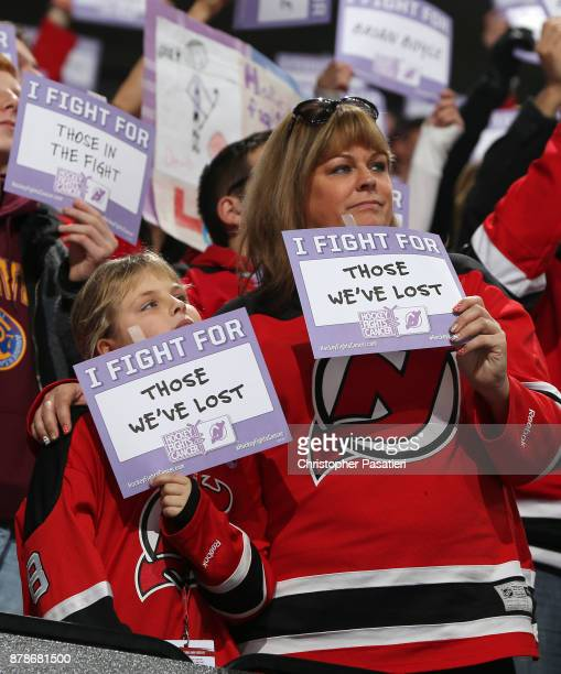 Fans hold up signs in support of Hockey Fights Cancer during the first period of the game between the Vancouver Canucks and New Jersey Devils on...