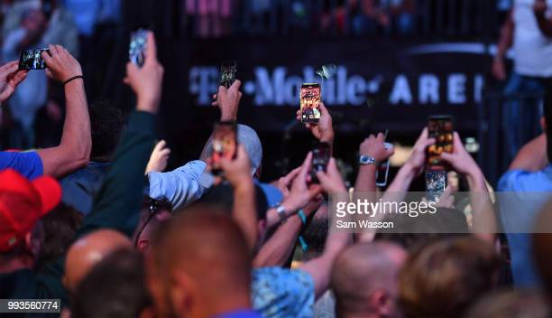 UFC fans hold up their cell phones as Stipe Miocic enters the arena before his heavyweight championship fight against Daniel Cormier at TMobile Arena...