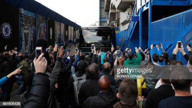 Fans hold up their smartphones as they gather to see the Chelsea team arrive ahead of the English Premier League football match between Chelsea and...