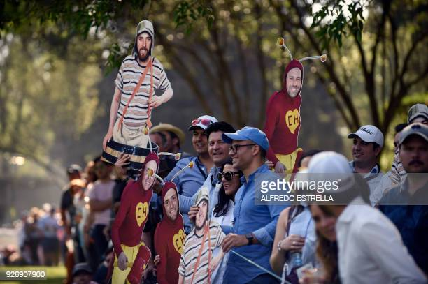 """Fans holding images of Mexican TV sitcom characters """"El Chavo del ocho"""" and """"El Chapulin colorado"""" with golfers' faces stand at green 16, during the..."""