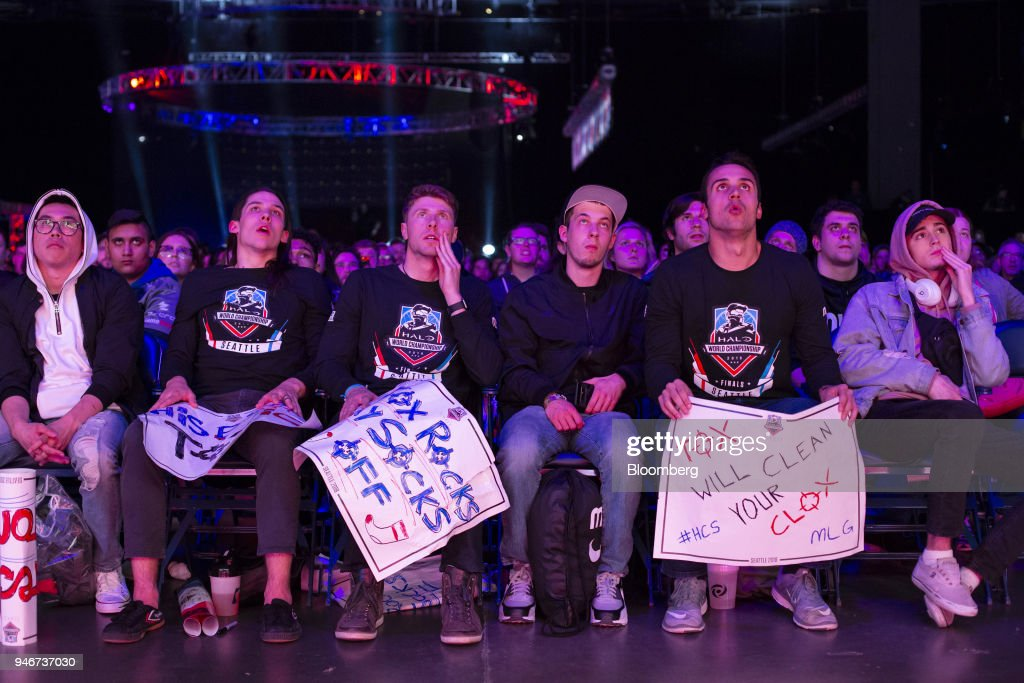 Fans holding placards watch the grand final game between teams Tox and Splyce during the Halo World Championship finals in Seattle, Washington, U.S., on Sunday, April 15, 2018. E-sports revenue, consisting of merchandise, event tickets, sponsorships, advertising and media rights -- all beyond game sales -- is expected to rise at a 32.2% average annual rate in 2016-20 to $1.5 billion in 2020, according to Newzoo. Photographer: David Ryder/Bloomberg via Getty Images