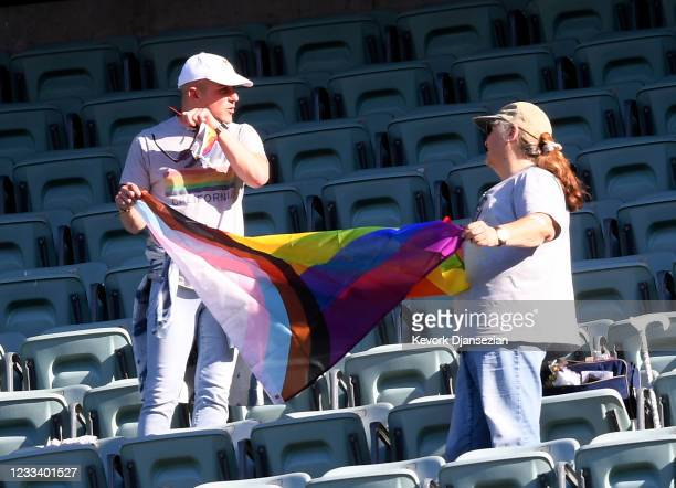 Fans holds a rainbow flag during eighth annual LGBTQ+ Night prior to start of a baseball game between the Los Angeles Dodgers and Texas Rangers at...