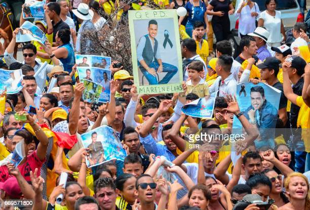 Fans holds placards with photographs of Colombian singer Martin Elias during his funeral in Valledupar northern Colombia on April 17 2017 The...