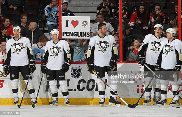 A fans holds up an I love Penguins sign as Robert Bortuzzo Jussi Jokinen Steve MacIntyre Simon Despres and Brenden Morrow warm up prior to a game...