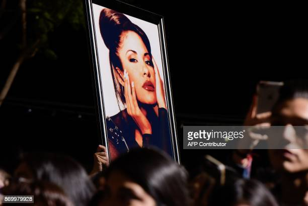 Fans hols a photo of Selena during the ceremony honoring singer Selena Quintanilla with a Star on the Hollywood Walk of Fame on November 3 in...