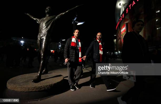 Fans in Arsenal scarves walk through a pool of light illuminating the Tony Adams statue ahead of the Carabao Cup Fourth Round match between Arsenal...