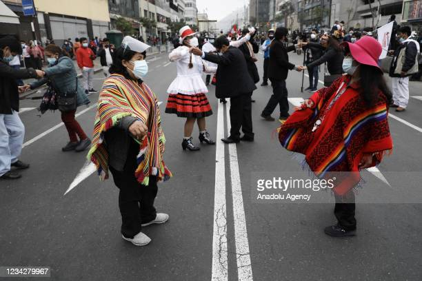 Fans in colorful clothing, people watching the presidential message on the street after inauguration of Pedro Catillo in Lima, Peru on July 28, 2021.
