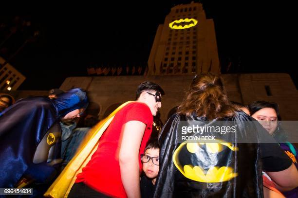Fans in costume get close to see the Batman 'Batsignal' projected onto Los Angeles City Hall in a tribute to the late actor Adam West June 15 in Los...