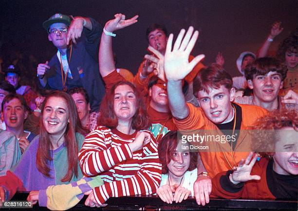 Fans in early 1990s indie fashions the front rows of the audience at a gig United Kingdom 1991