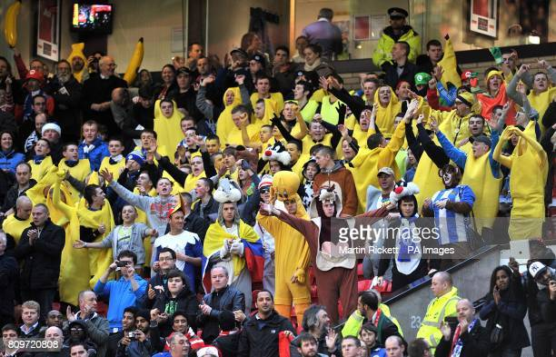 Fans in fancy dress cheer on their side in the stands on Boxing Day