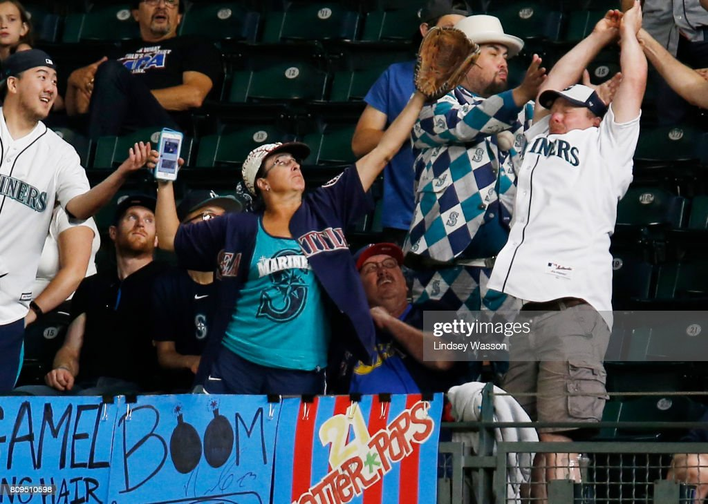 Fans in right field try and fail to catch the home run ball by Salvador Perez #13 of the Kansas City Royals in the tenth inning off of James Pazos #47 of the Seattle Mariners at Safeco Field on July 5, 2017 in Seattle, Washington.