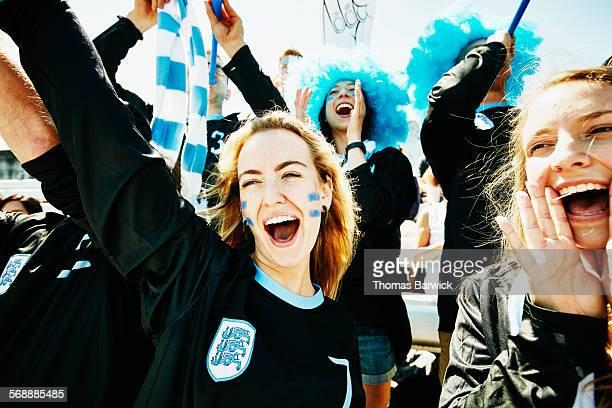 fans in team uniforms cheering during soccer match - liberty stadion stock-fotos und bilder