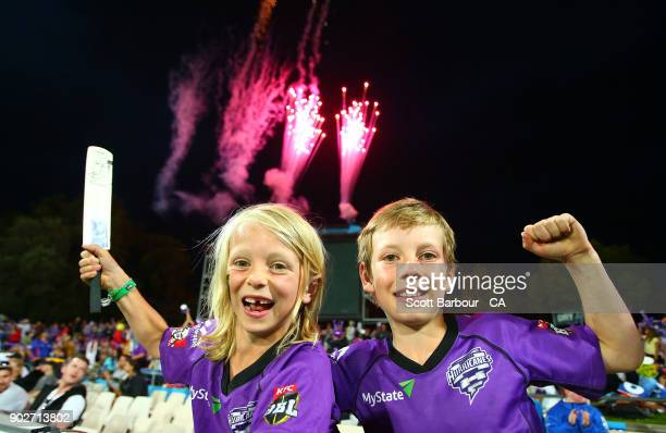 Fans in the crowd show their support as fireworks explode during the Big Bash League match between the Hobart Hurricanes and the Sydney Sixers at...